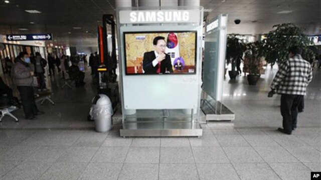 A TV screen shows South Korean President Lee Myung-bak's panel discussion at Seoul Railway Station in Seoul, South Korea, February 1, 2011