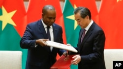 China's Foreign Minister Wang Yi, right, and Burkina Faso Foreign Minister Alpha Barry attend a signing ceremony establishing diplomatic relations between the two countries in Beijing, May 26, 2018.