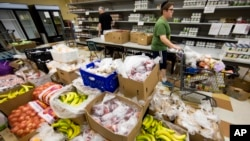 Volunteer David Bril, 13, puts together client Charles Scott's food selection, at the Mitzvah Food Project pantry at the Jewish Federation of Greater Philadelphia Digital Choice Food Program in Philadelphia, Pennsylvania, July 1, 2015.