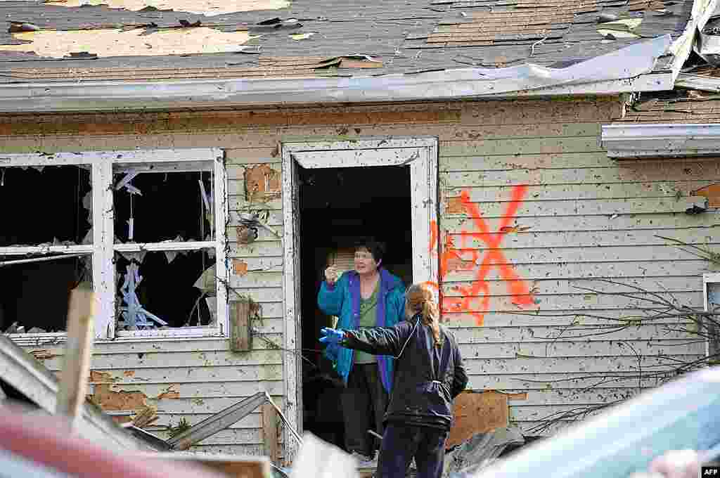 Margaret Shimkus, 61, talks with an emergency responder about her condition at her home in Harrisburg, Illinois, February 29, 2011. (AP)