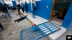 A guard lies dead inside the Civil Prison after a jail break in the coastal town of Arcahaiea, Haiti, Oct. 22, 2016.