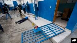 A guard lies dead inside the Civil Prison after a jail break in the coastal town of Arcahaiea, Haiti, Oct. 22, 2016.