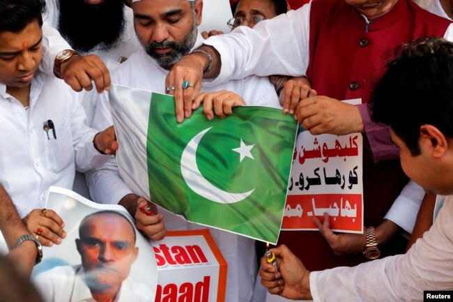 Supporters of the ruling Bharatiya Janata Party (BJP) burn Pakistan's national flag during a protest in Mumbai, against the death sentence given to former Indian naval officer Kulbhushan Jadhav in Pakistan, April 12, 2017.