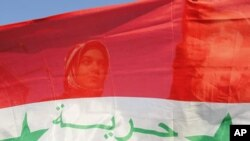 Syrian protesters stand behind a Syrian flag during a demonstration against Syria's President Bashar Al-Assad in front of the Syrian embassy in Amman, July 21, 2011