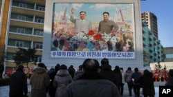 FILE - North Koreans gather in front of a portrait of their late leader Kim Il Sung, left, and Kim Jong Il, right, paying respects to their late leader Kim Jong Il, to mark the third anniversary of his death.