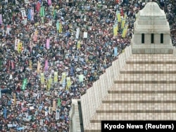 People hold placards and shout slogans as they gather to protest against Japan's Prime Minister Shinzo Abe's security bill outside the parliament in Tokyo, Aug. 30, 2015.