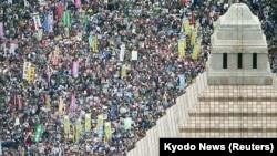 Orang-orang memegang poster dan meneriakkan slogan swat berkumpul untuk memprotes menentang rancangan undang-undang keamanan Perdana Menteri Jepang Shinzo Abe di luar gedung parlemen di Tokyo, 30 Agustus 2015.