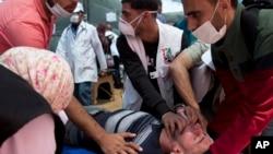 امدادگران در حال کمک به یک مجروح فلسطینی در نوار غزه