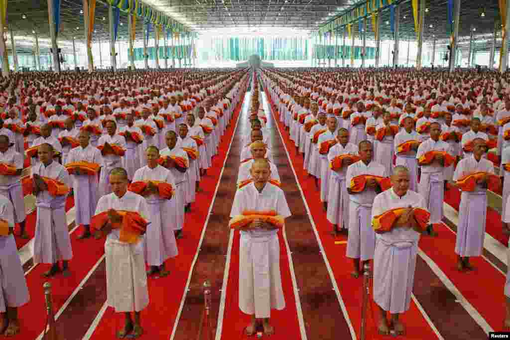Monks take part in a mass ordination ceremony for Buddhist Lent at the Wat Phra Dhammakaya temple in Pathum Thani province, north of Bangkok, Thailand, July 13, 2013.