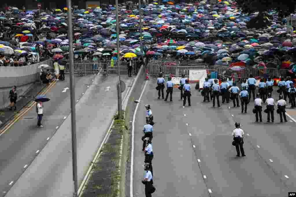2019年6月12日香港抗議者在立法會外反對逃犯條例修訂,警察在道路上巡邏。數以萬計的抗議者封鎖了主要道路,致使香港中部地區癱瘓。隨著人群繼續擴大,立法會表示推遲逃犯條例修訂二讀。