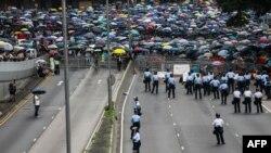 Seorang polisi menjaga jalan saat para pengunjuk rasa menggelar demonstrasi menentang RUU Ekstradisi yang kontroversial di luar kantor pemerintah di Hong Kong, 12 Juni 2019. (Foto: AFP)