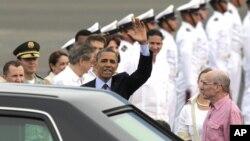 Prezidan Barack Obama ap salye foul la pandan li rive nan Katajèn. A dwat li, ambasadè ameriken an nan Kolonbi, Michael McKinley.