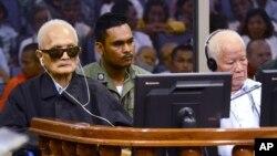23일 캄보디아 크메르루즈 정권의 '킬링필드' 전범들이 프놈펜 법정에 출두해 대법원의 판결 내용을 들고 있다.