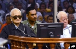 In this photo released by the Extraordinary Chambers in the Courts of Cambodia, the two most senior surviving members of the Khmer Rouge regime Nuon Chea, left, and Khieu Samphan listen to the verdict which upheld their life sentences.
