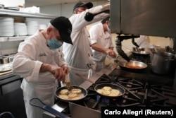 Chef Eksekutif Vito Gnazzo dari restoran Il Gattopardo menyiapkan hidangan pembuka mozzarella asap pada hari pertama restoran diizinkan untuk mulai bersantap di dalam ruangan sejak Covid-19 di Manhattan Borough of New York City, New York, AS, 30 September