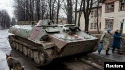 2015年3月13日德巴尔切夫城内,两名妇女走过一辆破损乌军装甲运兵车。