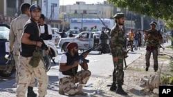 Anti-Gaddafi fighters take position during a gun battle with pro-Gaddafi's supporters in the Abu Salim neighborhood in Tripoli, Libya, October 14, 2011.