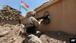 FILE - A Kurdish Peshmerga fighter is seen taking his position in a gun battle with Islamic State militants.