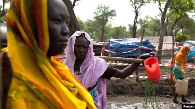 FILE - Women gather to collect water at the Yusuf Batil refugee camp in Upper Nile, South Sudan, July 4, 2012.