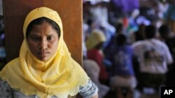FILE - A Rohingya woman stands at a temporary shelter in Bayeun, Aceh Province, Indonesia, Monday, June 1, 2015.