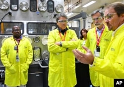U.S Secretary of Energy Rick Perry, second from left, accompanied by Laboratory Director Charlie McMillan, second from right, learns about capabilities at the Los Alamos National Laboratory's Plutonium Facility, from Jeff Yarbrough, right, Los Alamos associate director for plutonium science and manufacturing, in Los Alamos, N.M., May 10, 2017.