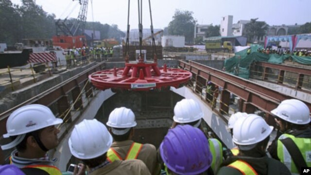 Employees watch as a tunnel boring machine is lowered at a construction site of the Delhi Metro Rail Corporation (DMRC) in Chelmsford Club in New Delhi, January 31, 2012.