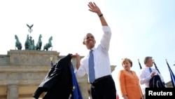 U.S. President Barack Obama waves next to German Chancellor Angela Merkel (C) and Berlin Mayor Klaus Wowereit (R) after giving a speech in front of the Brandenburg Gate in Berlin June 19, 2013. Obama's first presidential visit to Berlin comes nearly 50 ye