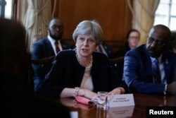 FILE - Britain's Prime Minister Theresa May hosts a meeting with leaders and representatives of Caribbean countries, at 10 Downing Street in London, April 17, 2018.