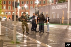 Police officers and a soldier stand by the sealed off area of an attack after a truck drove on to the sidewalk and plowed through a crowd of revelers who'd gathered to watch the fireworks in the French resort city of Nice, southern France, Friday, July 15, 2016.