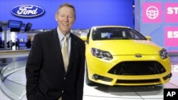 FILE - Ford President and CEO Alan Mulally stands by a Ford Focus during the North American International Auto Show in Detroit, Jan. 15, 2013.