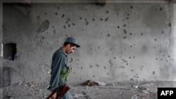 Cảnh sát Afghanistan đi ngang qua một bức tường có nhiều dấu vết đạn tại Kabul