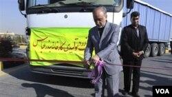 Kepala Badan Energi Atom Iran, Ali Akbar Salehi, memotong sebuah pita peresmian di fasilitas pengolahan uranium di Isfahan, dengan truk di belakangnya berisi bubuk uranium produksi dalam negeri Iran.