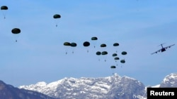 FILE - A U.S. Air Force C-17 Globemaster III from the 97th Air Mobility Wing plane drops paratroopers during an exercise over the NATO airbase in Aviano, Italy.