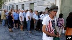 Warga Yunani, sebagian besar para pensiunan, antri di depan kantor cabang bank nasional Yunani di Athena, Senin (20/7).