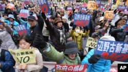 """FILE - Anti-U.S. base protesters hold placards with a slogan that reads: """"No to Henoko new base"""" during a rally in Tokyo Nov. 29, 2015. Protesters showed their strong support to Okinawans after the Japanese government took the local government in Okinawa to court in mid-November."""
