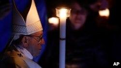 El papa Francisco sostiene una vela mientras preside la solemne ceremonia de Vigilia Pascual en la Basílica de San Pedro, en el Vaticano, el sábado, 31 de marzo, de 2018.