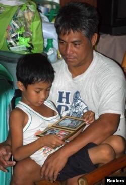 Cedric Caubalejo, 8 tuổi, xem hình mẹ trong lúc ngồi với cha tại Manila.