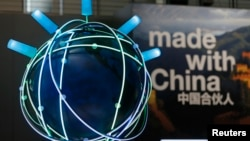 FILE - The motto of the 2015 CeBit trade fair ' Made With China' is seen next to a rotating globe at the IBM booth during the fair in Hanover, Germany, March 16, 2015.