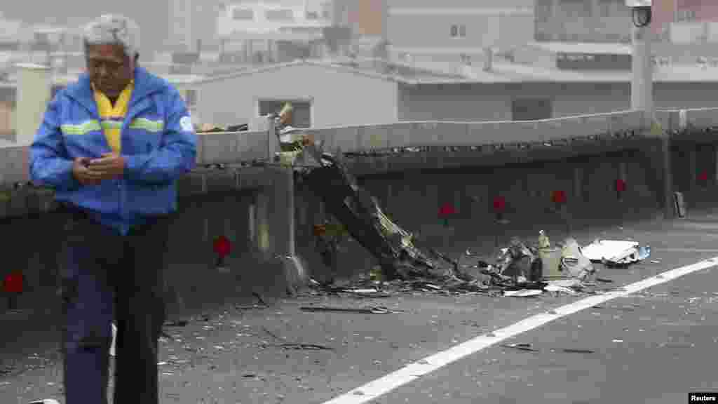 A man walks past next to the wreckage of a TransAsia Airways plane which hit a motorway before crash landing in a river, in New Taipei City.