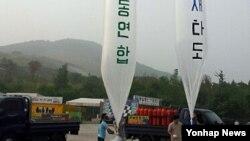 15일 경기도 파주시 통일동산 주차장에서 탈북자단체인 자유북한운동연합이 대북전단을 대형 풍선에 매달아 날려 보내고 있다.