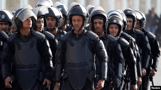 FILE - Riot police take their positions outside a police academy, where ousted Egyptian President Mohamed Morsi's second trial session was due to take place outside Cairo on January 8, 2014.