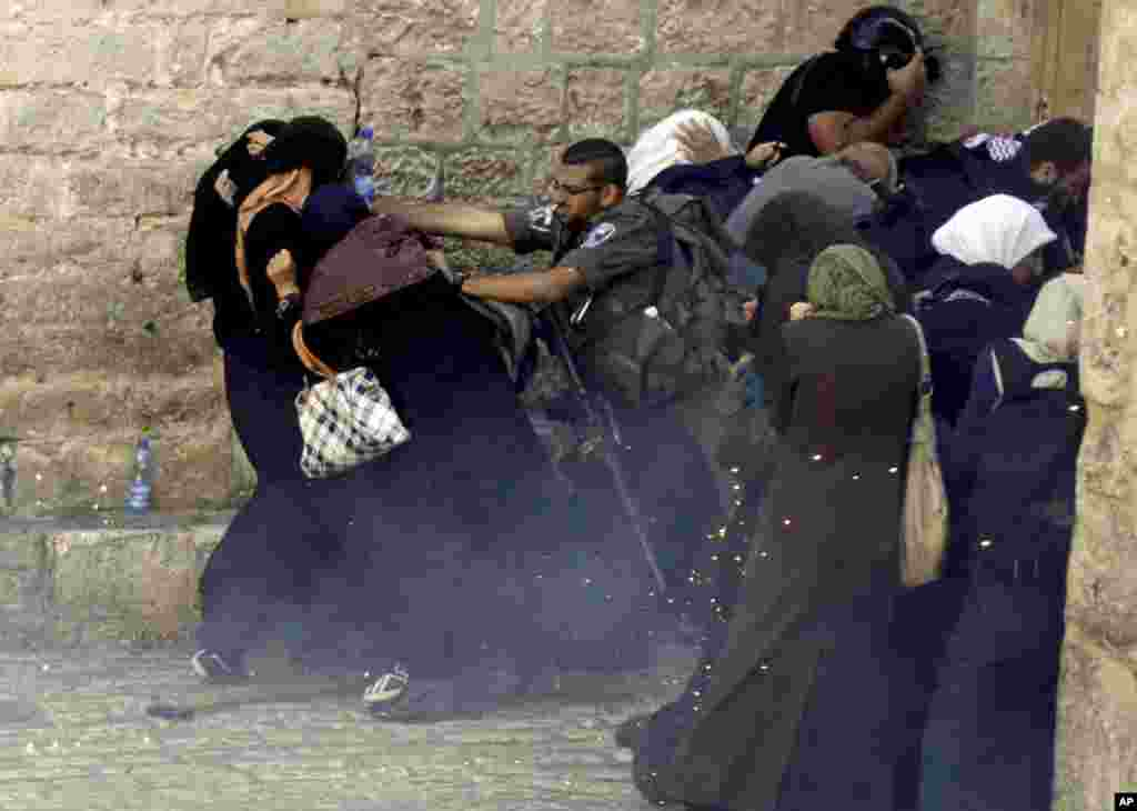 Israeli border policeman pushes Palestinian women during clashes in the Old City of Jerusalem. Israeli police clashed with young Palestinian protesters demonstrating against Jews visiting the Al-Aqsa Mosque compound, Islam's third holiest site, a spokeswoman said.