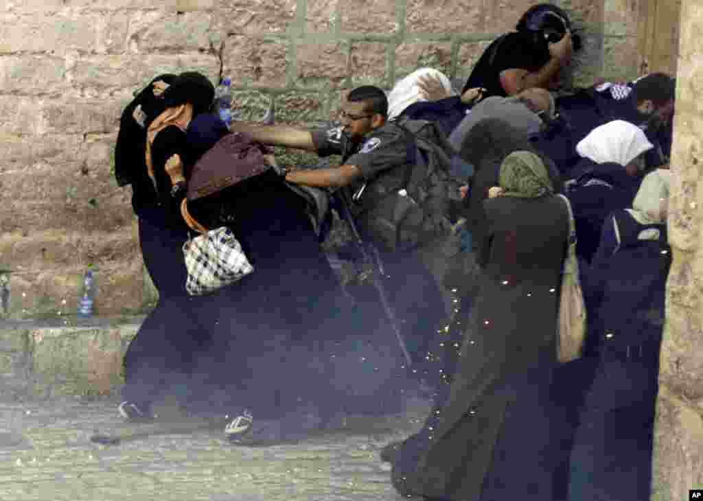 예루살렘 구 시가지에서 이스라엘 국경 수비대원이 팔레스타인 시위대를 밀어내고 있다. 팔레스타인 주민들은 이슬람 3대 성지인 알-아크사 사원에서 유대교도들의 방문을 거부하며 시위를 벌였다.