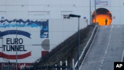 A railway worker walks past the entrance to the Channel Tunnel near Calais in Coquelles, France, Jan.17, 2015.