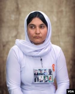 Shireen Jardo talks about her enslavement by the Islamic State during an interview with Voice of America. She wears a poster with pictures of her three brothers and five other members of her extended family still missing in IS territory.