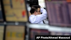 A currency trader watches monitors at the foreign exchange dealing room in Seoul, South Korea, March 27, 2017