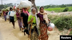 FILE - Rohingya refugees, who crossed the border from Myanmar two days earlier, walk after they received permission from the Bangladesh army to continue their way to Kutupalong refugee camp, near Cox's Bazar, Bangladesh, Oct. 19, 2017.