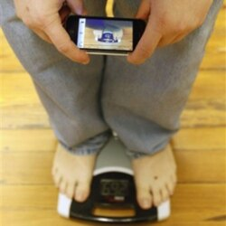 A man uses a smartphone to photograph and track his weight on a scale in his office in Pennsylvania