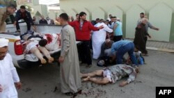 15일 이라크 북부 키르쿠크의 이슬람 사원에서 폭탄 공격이 발생한 가운데, 주민들이 희생자의 시신을 수습하고 있다.