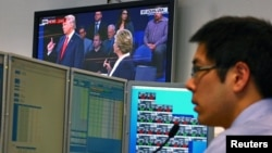 A trader works at his desk as the U.S. presidential town hall debate between Republican U.S. presidential nominee Donald Trump and Democratic nominee Hillary Clinton is shown on TV, at Citibank's trading floor in Sydney, Australia, Oct. 10, 2016.